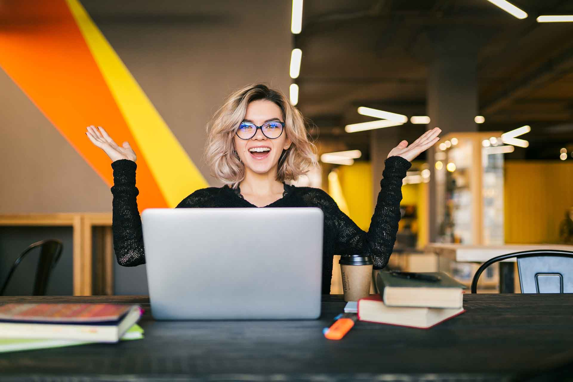 in raise funny happy excited young pretty woman sitting table black shirt working laptop co working office wearing glasses
